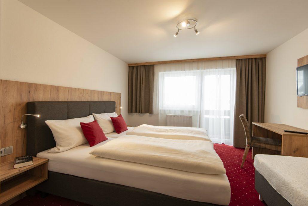 Hotelzimmer roter Teppich antracietes bed und Moebel aus Holz