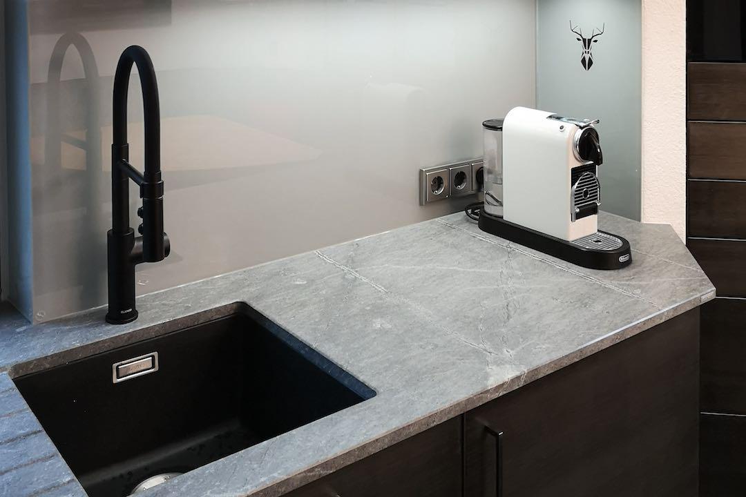 Stahlkueche mit schwarzes Waschbecken und Wasserhahn